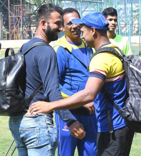 Saurashtra's Cheteshwar Pujara (left) and Karnataka's Mayank Agarwal greet each other at the KSCA (B) Ground on Tuesday. DH Photo/ Srikanta Sharma R