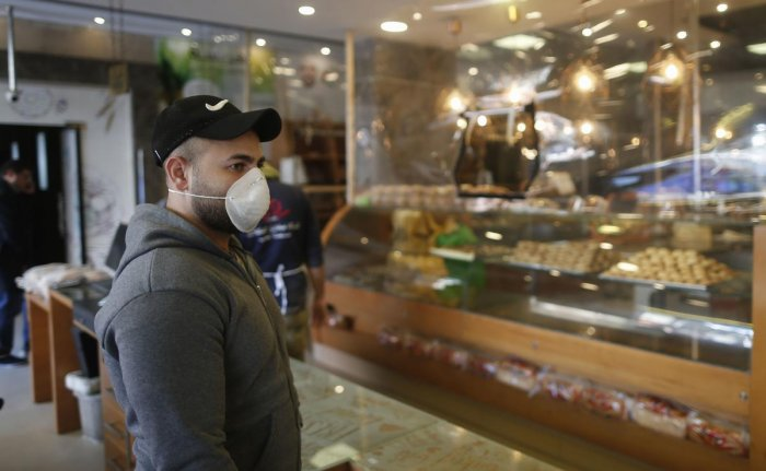 A Palestinian man wearing a protective face-mask waits in a bakery in Gaza City. AFP