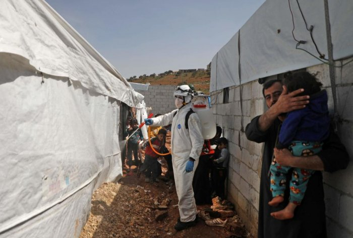 """A member of the Syrian Civil Defence, also known as the """"White Helmets"""", disinfects a tent in the Kafr Lusin camp for the displaced by the border with Turkey, in Syria's rebel-held northwestern province of Idlib, on March 24, 2020, as part of efforts to prevent the spread of coronavirus. Credit: AFP Photo"""