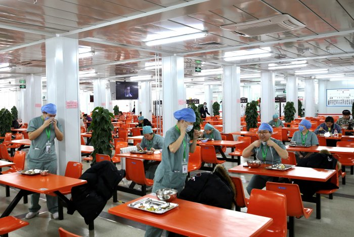 Medical workers eat at separate tables at a canteen inside Xiaotangshan Hospital, a hospital built in 2003 to treat patients with Severe Acute Respiratory Syndrome (SARS) that is now used to treat patients with coronavirus disease (COVID-19), in Beijing. (Reuters file photo)