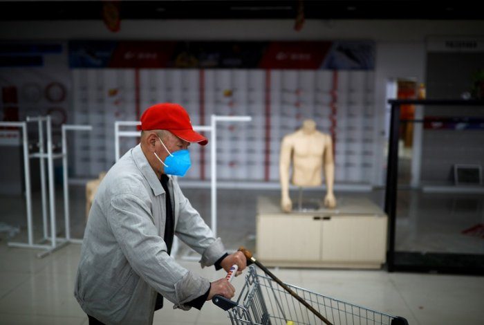 man pushes a shopping cart past a stall that had to close because its owners could not return from his home in the province, as the spread of the coronavirus disease (COVID-19) continues, in Beijing, China. (Reuters Photo)