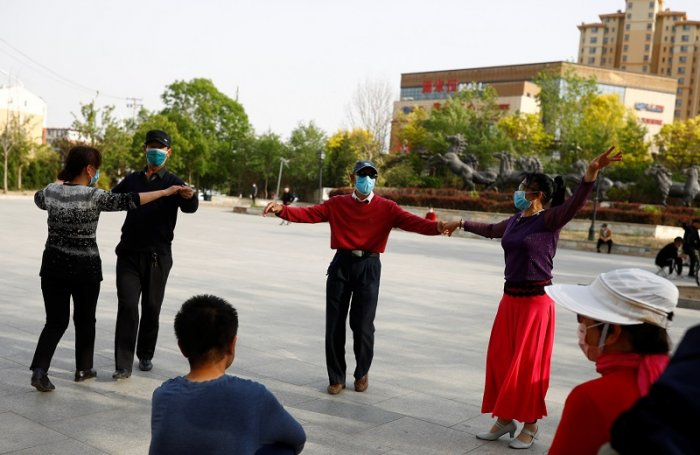 People wearing face masks dance at a public square, as the spread of the coronavirus disease (COVID-19) continues, in Beijing. (Reuters Photo)