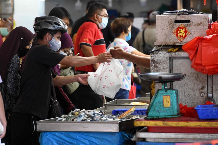 A man, wearing a face mask as a preventive measure against the spread of the COVID-19 novel coronavirus, makes a purchase at a fish stall in Geylang Serai wet market in Singapore. (Credit: AFP Photo)