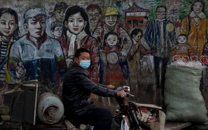 A man wearing a face mask amid concerns of the COVID-19 coronavirus drives his motorbike along a street in Wuhan (AFP photo)