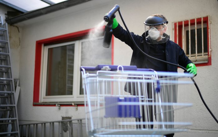 Working student Leon Rottmann coats a shopping trolley for disinfection at the mechanic's workshop of the Startup UVIS UV-Innovative Solutions in Cologne, western Germany. (AFP)