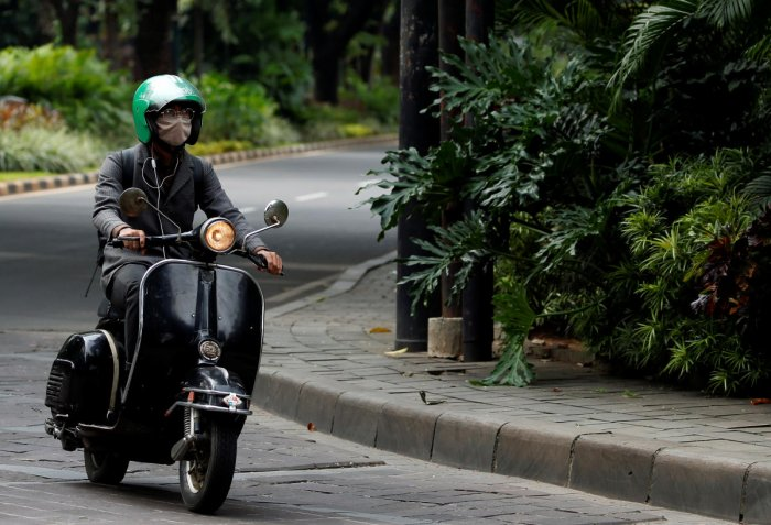 A man wearing a protective mask rides a scooter trough a deserted road during the large-scale restrictions imposed by the government to prevent the spread of the coronavirus disease (COVID-19), in Jakarta, Indonesia, April 25, 2020. Reuters