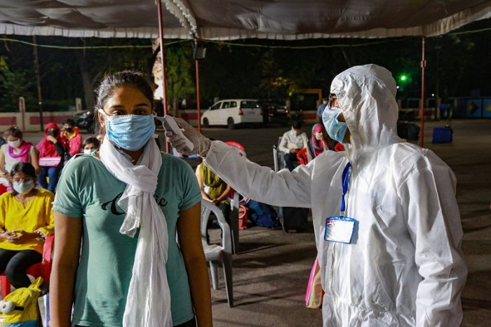 A medic checks the temperature of a stranded student from Kota upon her arrival, during the nationwide lockdown to curb the spread of coronavirus, in Indore. (PTI Photo)