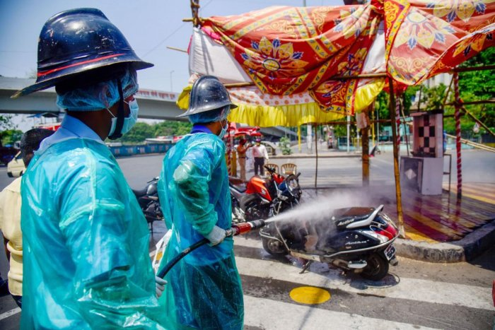 Firefighters spray disinfectant on a scooter as a preventive measure to curb the spread of coronavirus, during the nationwide lockdown, at Swargate chowk, in Pune, Friday, April 17, 2020. (PTI Photo)
