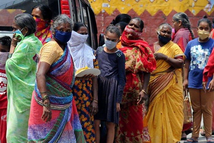 People queue up to collect food at Swami Vivekananda Road, Halasuru, on Friday. DH Photo/Pushkar V