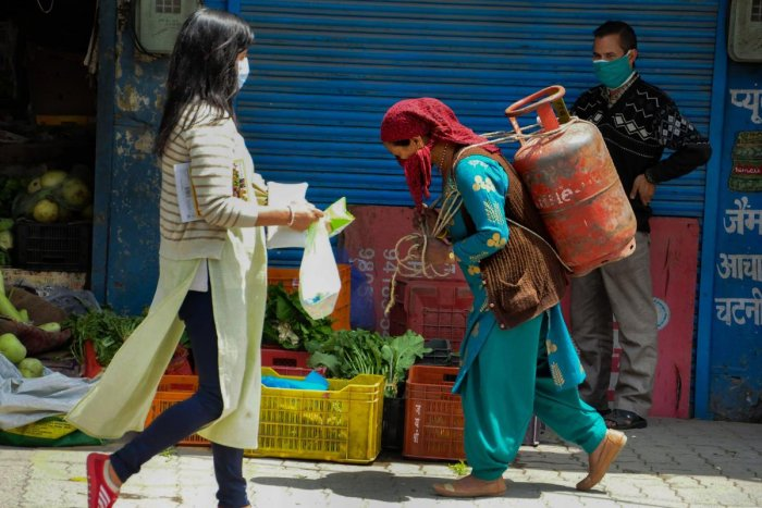 A woman carries a LPG cylinder on her back as another woman walks past her, during the nationwide lockdown to curb the spread of coronavirus, in Kullu, Monday, April 27, 2020. (PTI Photo)