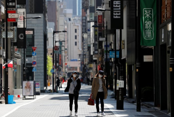 Women wearing face masks walk in a deserted shopping district during the nationwide state of emergency following the coronavirus disease (COVID-19) outbreak in Tokyo. Reuters