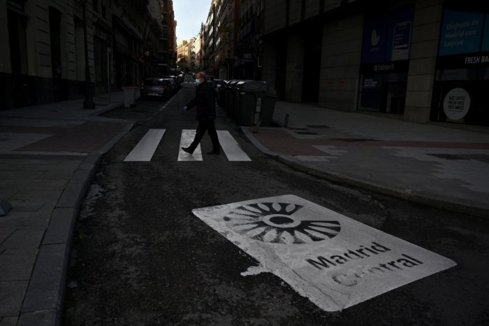 A man crosses a street in Madrid, on April 24, 2020 amid a national lockdown to fight the spread of the coronavirus. AFP
