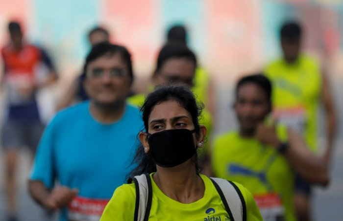 A runner wearing a face mask for protection from air pollution takes part in the Airtel Delhi Half Marathon in New Delhi. (Reuters Photo)