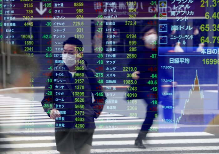 Passersby wearing protective face masks following an outbreak of the coronavirus disease (COVID-19) are reflected on a screen displaying stock prices outside a brokerage in Tokyo. (Credit: Reuters)