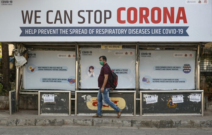 A man wearing a protective mask walks past a bus stop displaying preventive measures against the coronavirus in Mumbai. (Credit: Reuters)