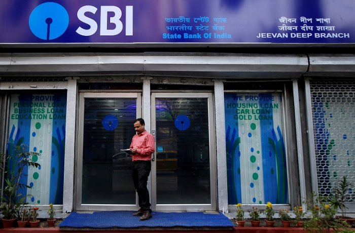 A man checks his mobile phones in front of State Bank of India (SBI) branch in Kolkata, India. (Reuters Photo)