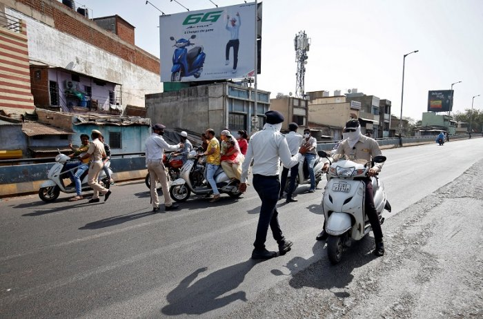 Policemen stop people travelling on scooters after the lockdown by Gujarat state government to limit the spreading of coronavirus disease. (Reuters Photo)