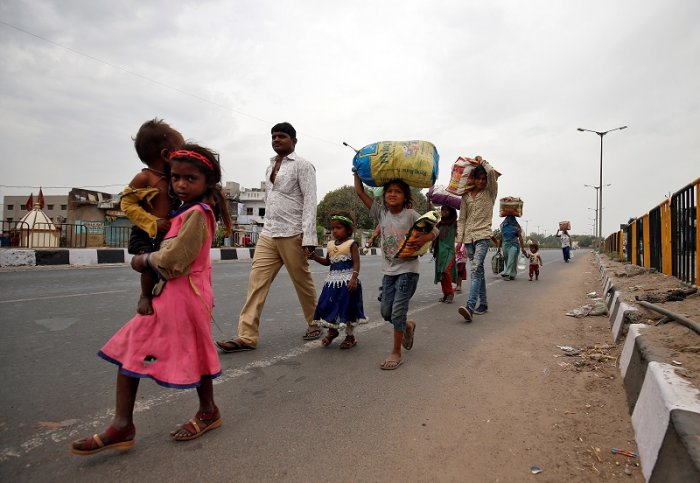 Migrant workers walk with their children as they look out for transport to return to their villages, after India ordered a 21-day nationwide lockdown to limit the spreading of coronavirus disease (COVID-19), in Ahmedabad, India. (Reuters Photo)