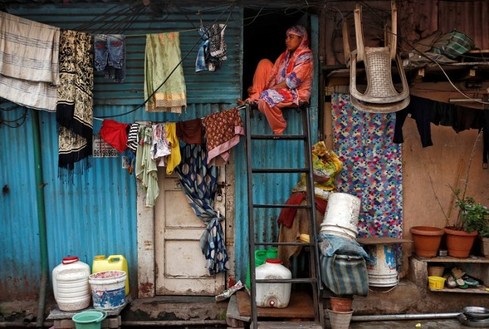 A woman sits on a ladder installed outside her house, during a nationwide lockdown in India to slow the spread of COVID-19, in Dharavi. (Reuters Photo)
