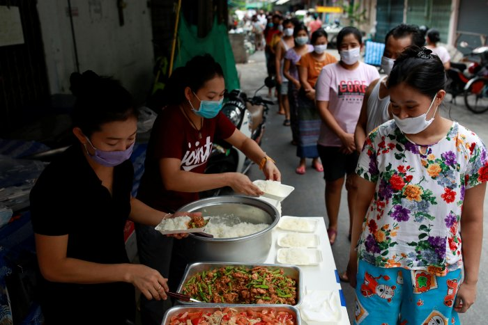 Volunteers give free foods for migrant workers from Myanmar who lost their jobs following the coronavirus disease. (Credit: Reuters Photo)