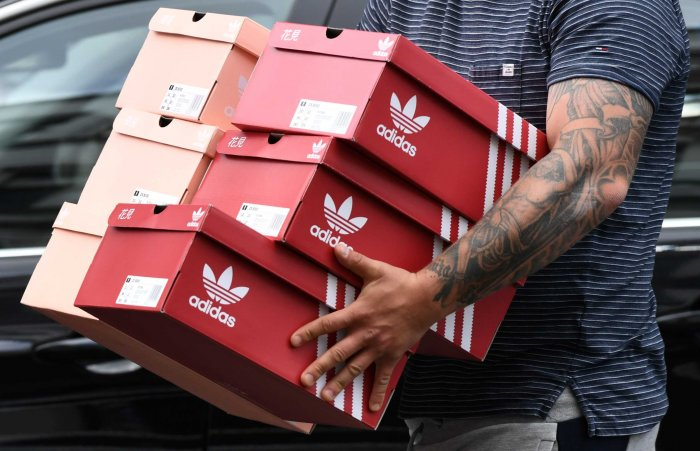 A man carries Adidas shoeboxes near the Adidas store, as the spread of the coronavirus disease (COVID-19) continues, in Berlin, Germany (Credit: Reuters)