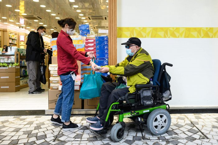 This photo taken on February 13, 2020 shows muscular atrophy patient Steven Yan (R) buying a bag of paper towels from a pharmacy in the Sheung Shui district of Hong Kong. (Credit: AFP Photo)