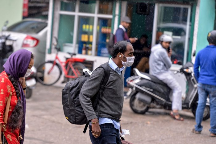 Travellers wear facemasks as they walk at the Sikkim Nationalised Transport (SNT) parking, following a ban put by the Sikkim government on all foreign tourists travelling from other countries to Sikkim state due to the COVID-19 coronavirus outbreak. (AFP Photo)