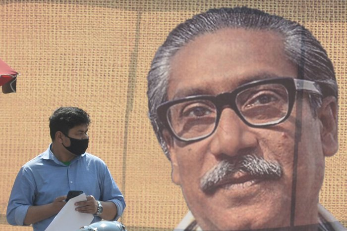 A man wearing a facemask amid fears of the spread of COVID-19 novel coronavirus, walks past a banner with a picture of Bangladesh's founder Sheikh Mujibur Rahman. (AFP Photo)