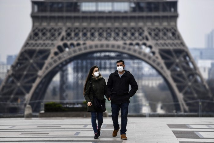 A couple wearing protective mask walks by the Esplanade du Trocadero square near the Eiffel Tower in Paris (AFP photo)