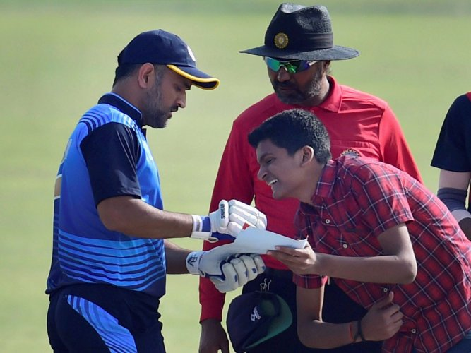 Another 1st: Dhoni signs autograph while batting in middle