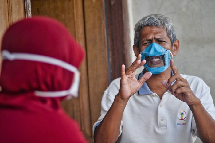 Dwi Rahayu (L) and her husband Elfiandi who are deaf and mute communicate while wearing face masks with a transparent cover in Yogyakarta (AFP)