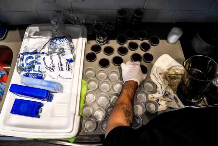 Rafael Delgado (29), who used to work as an Uber driver and recently found himself unemployed, prepares containers of dipping sauce to serve with homemade tequenos, a popular Venezuelan snack, inside his home in Miami. (AFP)