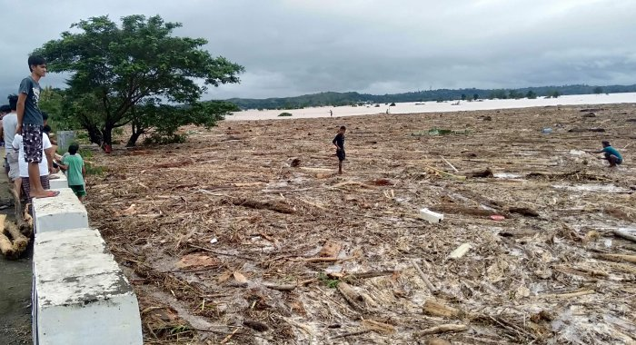 Residents walk on a rice field with washed up debris caused by Typhoon Kammuri in Ilagan. (AFP Photo)