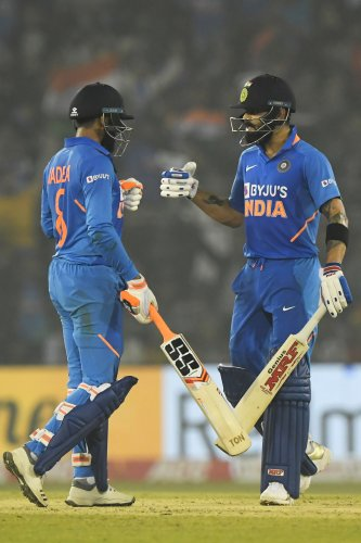 India's Ravindra Jadeja (L) clebrates after scoring a boundary with captain Virat Kohli during the third one day international cricket match of a three-match series between India and West Indies at the Barabati Stadium in Cuttack. (AFP Photo)