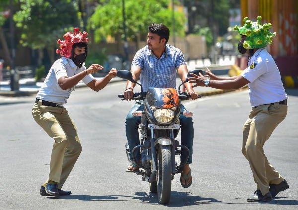 Two policeman wearing coronavirus-themed helmets charge another ríding a bike during an awareness programme amid the nationwide lockdown in the wake of novel coronavirus pandemic, in Bengaluru, Tuesday, Mar 31, 2020. (PTI Photo/Shailendra Bhojak)