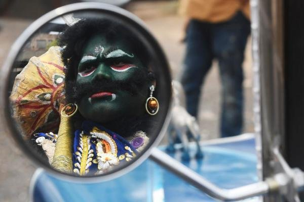 The reflection of a man dressed as Hindu deity of death Yamaraj (R) to raise awareness about the coronavirus is seen on the wing mirror of a vintage car during a government-imposed nationwide lockdown as a preventive measure against the COVID-19 coronavirus, in Kolkata on April 24, 2020. (Credit: AFP Photo)