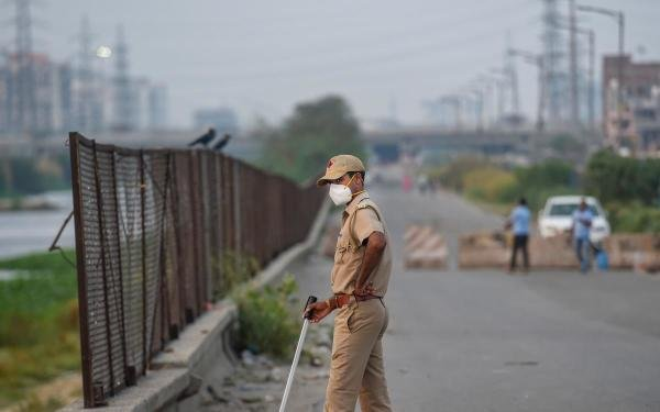 A policeman wearing a mask stands guard on a road at Ghazipur during the nationwide lockdown, imposed in wake of the coronavirus pandemic, in New Delhi, Monday, April 27, 2020. (PTI Photo/Atul Yadav)