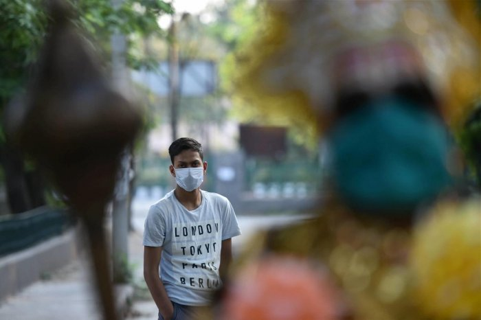A masked man looks at Baldev Singh who is dressed as Yama, the Hindu god of death, during an awareness campaign to educate people on staying indoors amid the nationwide lockdown, in wake of the coronavirus pandemic, at RK Puram in New Delhi, Tuesday, April 28, 2020. Credit: PTI Photo