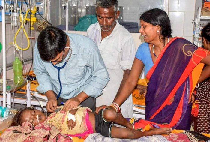 A doctor treats a child showing symptoms of Acute Encephalitis Syndrome (AES) at a hospital in Muzaffarpur, Tuesday, June 11, 2019. At least a dozen children in the city have died due to the disease while many others are being treated in several hospitals. (PTI Photo)