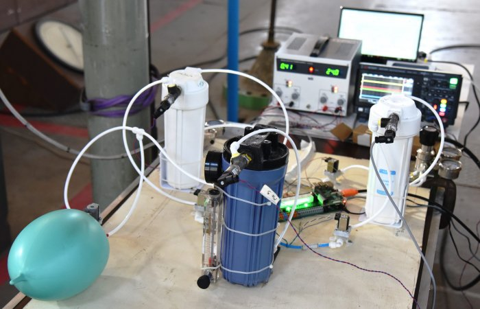 A benchtop test setup of a ventilator prototype being built by IISc scientists and volunteers at IISc's High-Speed Wind Tunnel Complex.The prototype is created out of components from the Indian automotive and RO filter industry. The white canisters contain air and o2, which are mixed in the blue cylinder. The control circuitry is composed of PCL board and Raspberry Pi. The medical test lung is for experimentation testing only. (Photo courtesy IISc Project Praana Team)