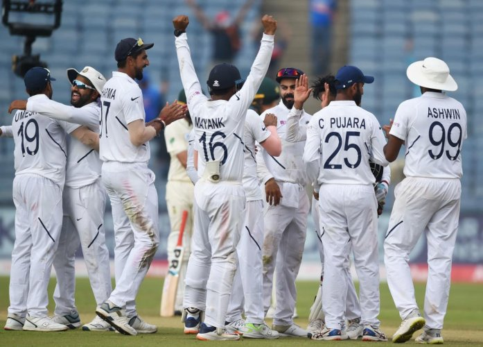 Indian cricketers celebrate on the fourth day of play after winning the second Test cricket match against South Africa at the Maharashtra Cricket Association Stadium in Pune on October 13, 2019. (Photo by PUNIT PARANJPE / AFP)