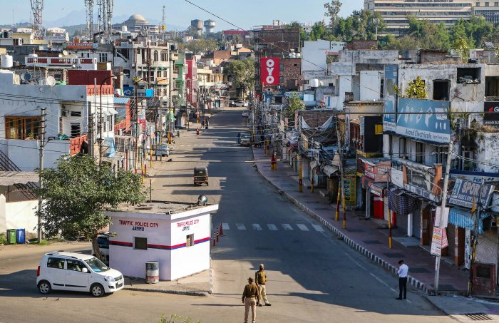 Security personnel wearing protective face mask stand guard on a deserted city street during 'Janata curfew' in the wake of coronavirus pandemic, in Jammu, Sunday, March 22, 2020. (PTI Photo)