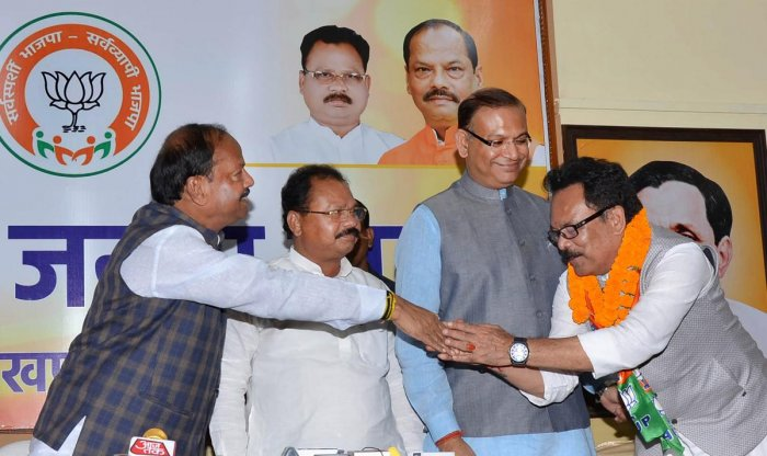 Jharkhand Chief Minister Raghubar Das shakes hand with Congress MLA Sukhdeo Bhagat after the latter joined BJP during 'Milan Samaroh' programme, in Ranchi, Wednesday, Oct. 23, 2019. (PTI Photo)