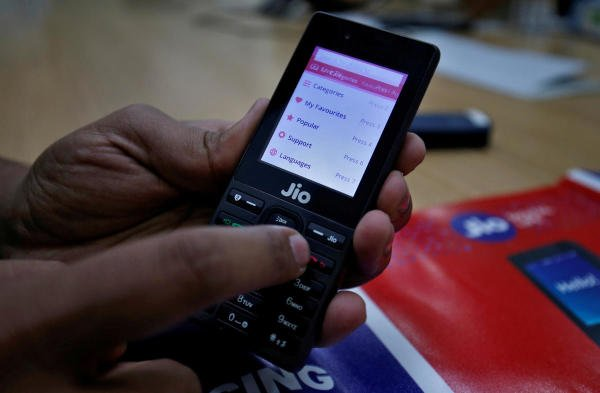 A sales person displays features of JioPhone as he poses for a photograph at a store of Reliance Industries' Jio telecoms unit. (Reuters photo)