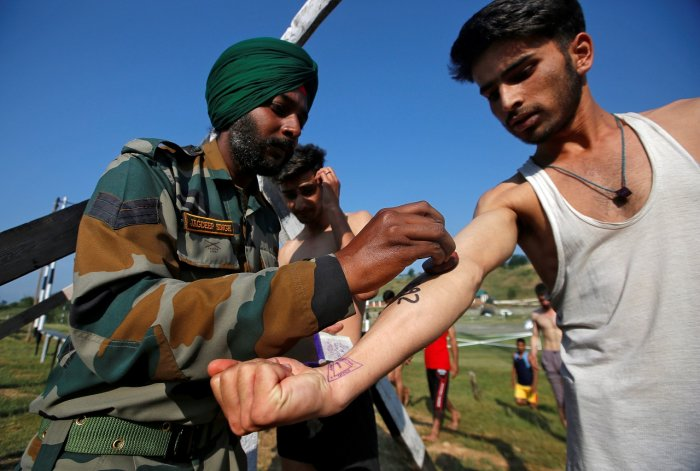 An army soldier stamps the arm of a Kashmiri youth during a recruitment drive organized by the Indian army in Pattan, north of Srinagar, earlier this month (PTI File Photo)