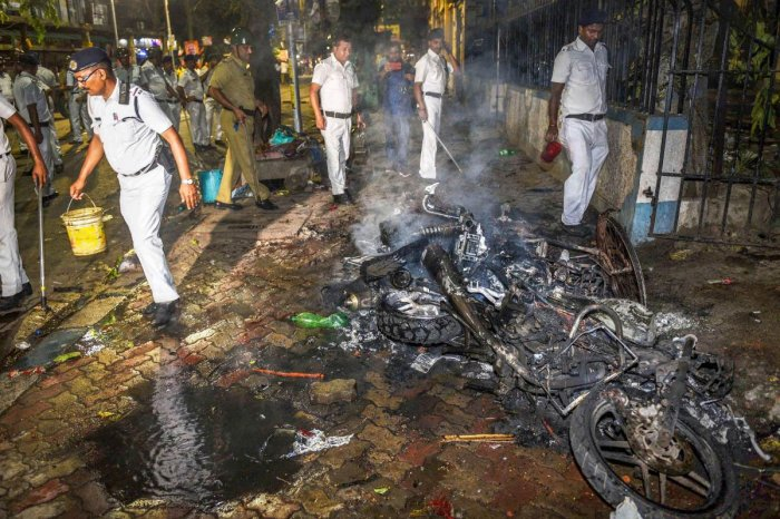 Police personnel douse burning vehicles caused by a mob during BJP President Amit Shah's election roadshow for the last phase of Lok Sabha polls, in Kolkata, Tuesday, May 14, 2019. (PTI Photo)