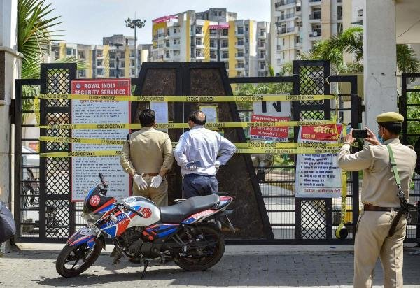 Police personnel outside the sealed KDP Grand Savanna society, marked as a COVID-19 hotspot, during the nationwide lockdown to curb the spread of coronavirus, at Rajnagar Extension in Ghaziabad. (Credit: PTI Photo)