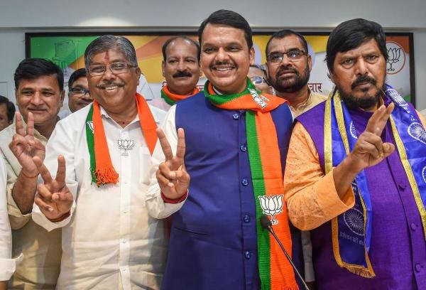 Maharashtra Chief Minister Devendra Fadnavis, State BJP president Chandrakant Patil and RPI chief Ramdas Athawale flash victory signs as they celebrate their win in Maharashtra Assembly elections, in Mumbai. (PTI photo)