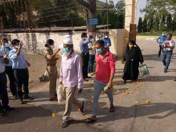 Medical staff and police personnel shower flower petals on COVID-19 patients as they leave the hospital after recovering, during the nationwide lockdown, at Malegaon in Nashik, Monday, April 27, 2020. (PTI Photo)