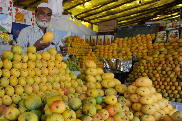 A mango seller arranges different variety of fruits at his stall on TV Tower Road near Jayamahal in Bengaluru on Friday. What once housed 150 mango stalls has come down to just two due to the lockdown. DH Photo/ Pushkar V